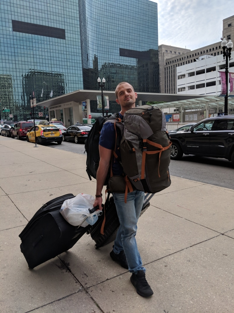 Handsome guy (me) carrying four backpacks and suitcases down the street