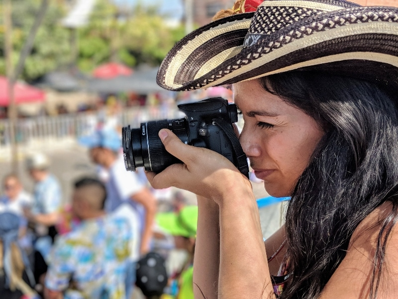 Woman photographer at Carnaval - Travel photography is one of the best travel jobs (and most common)