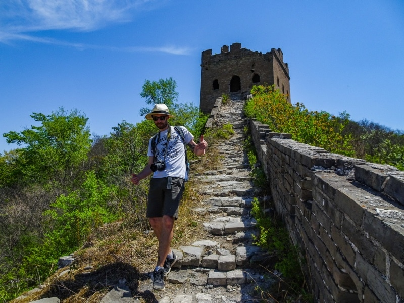 Man hiking through ruins with camera
