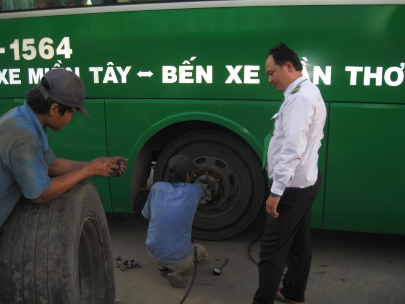 Man fixing flat tire of bus