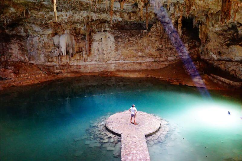 Man standing inside beautiful cenote in Mexico