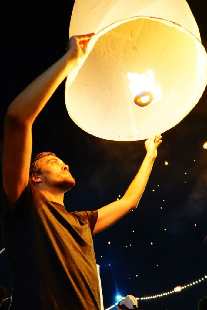 Man lighting lantern during Lantern Festival in Chian Mai, Thailand