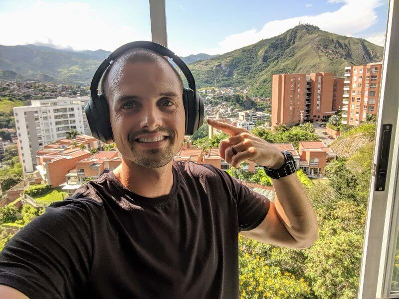 Man wearing Sony WH1000XM3 headphones with nice mountain view of Cali, Colombia in background