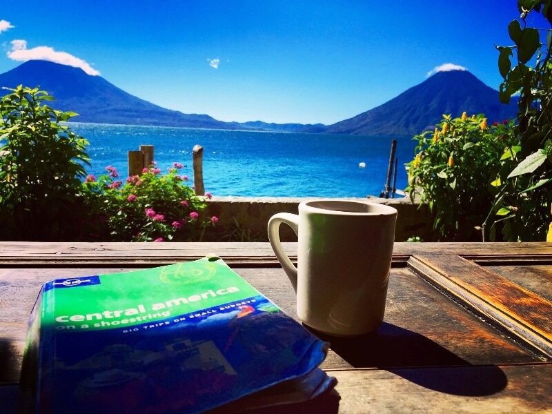 A lonely planet travel guide—one of the best gifts for travelers—sitting on  a table overlooking Lake Atitlan, Guatemala
