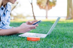 Person using Skyroam mobile wifi on his laptop in the grass