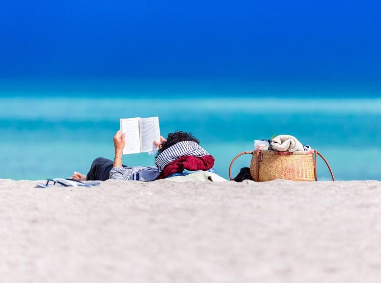 best books for travel lovers feature image - guy reading a book on the beach