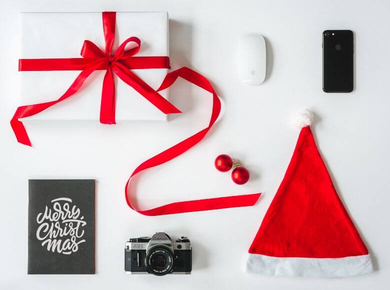 christmas gifts for travelers feature image - presents and holiday items laid out on table