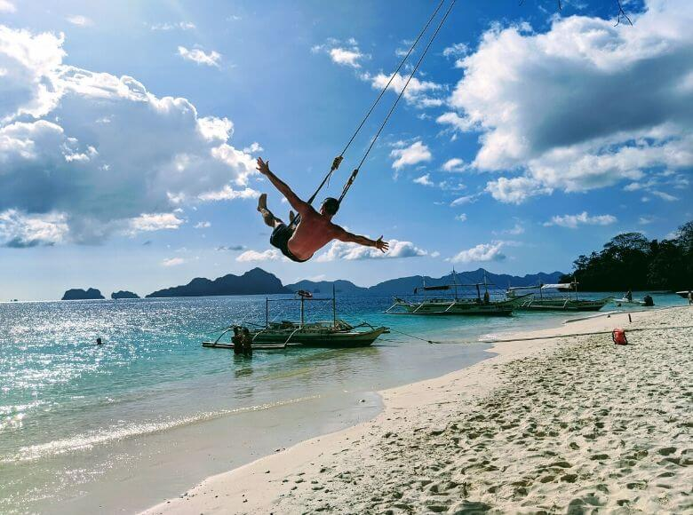 man on swing at the beach