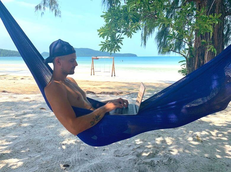 gifts for digital nomads feature image - man working from a hammock on the beach