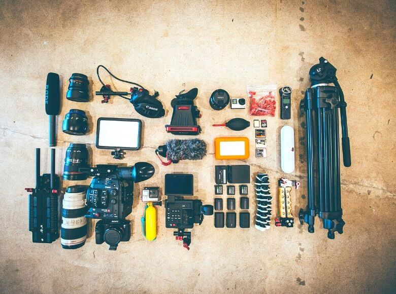 best gifts for photography lovers feature image - camera equipment laid out on the floor