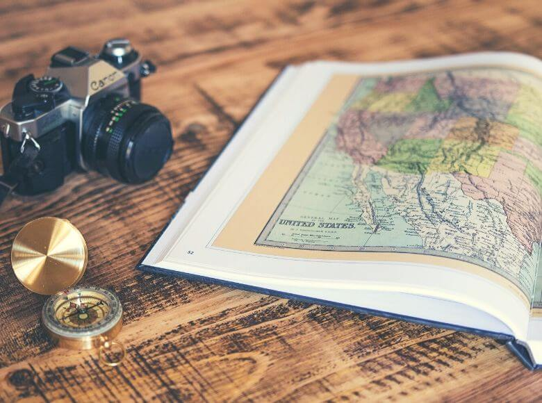 gifts for retired travelers feature image - map book, compass, and camera laid out on table