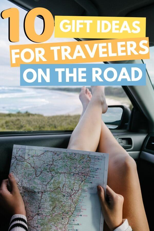 person sticking feet out car window looking at map with text overlay 10 gift ideas for travelers on the road