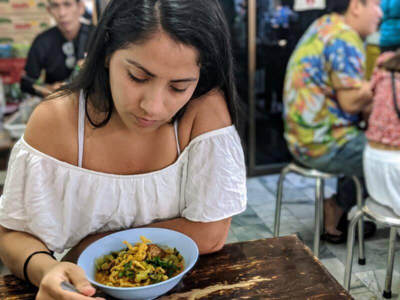 girl eating Khao Soi in Chiang Mai, Thailand
