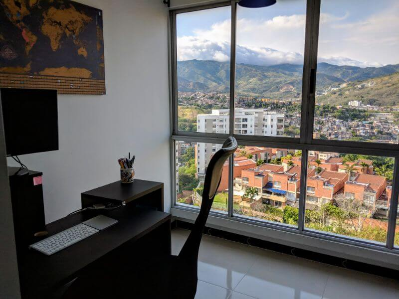 office in Cali Colombia with scratch map poster on wall and view of city