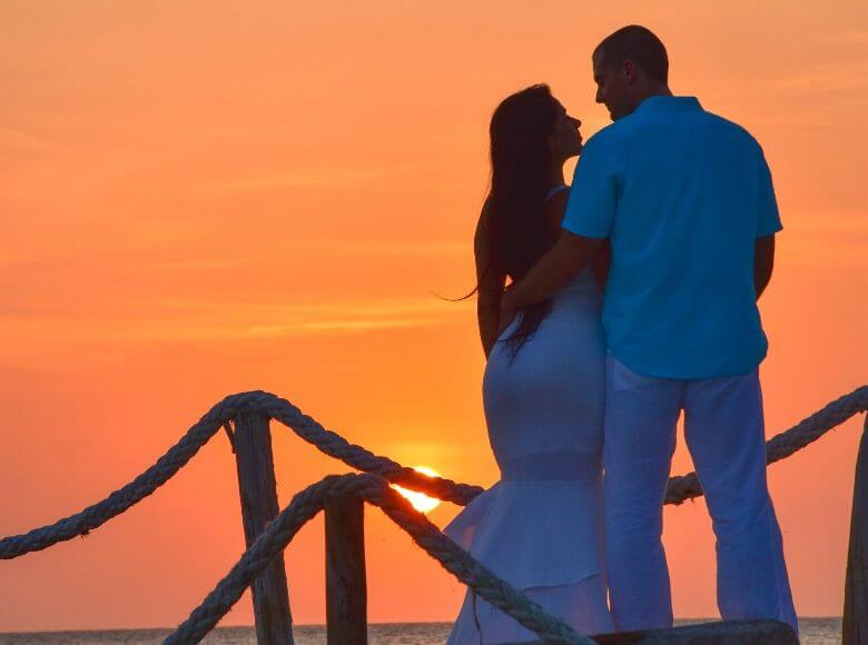 travel gifts for couples feature image - man and woman looking into each other's eyes at sunset