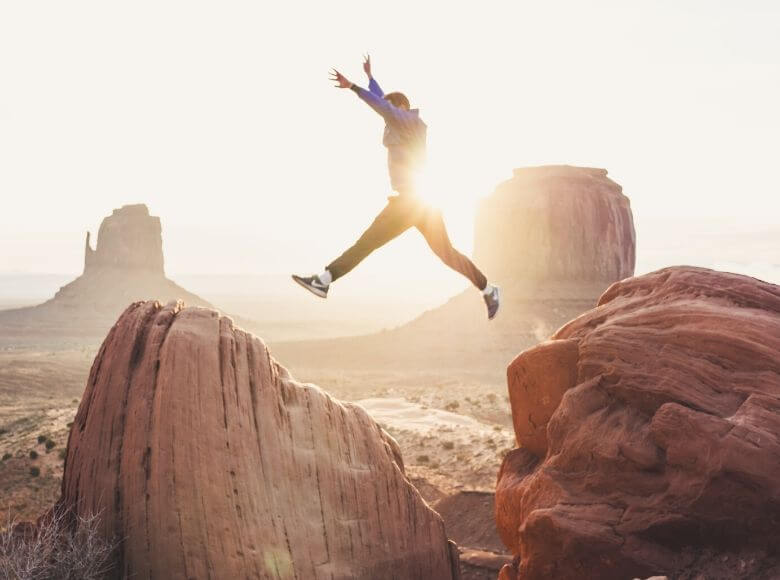 unique travel gifts for men feature image - man jumping between two big rocks in the desert