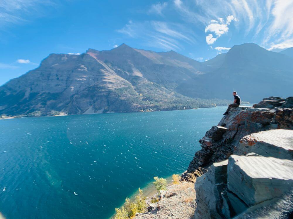 man sitting on ledge at glacier national park in montana
