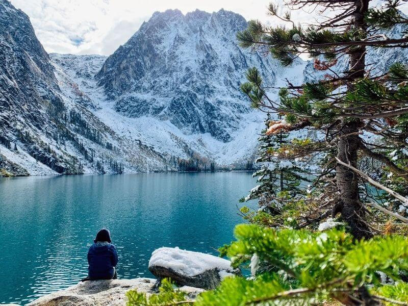 woman sitting in front of beautiful Colchuck Lake and mountains in Washington