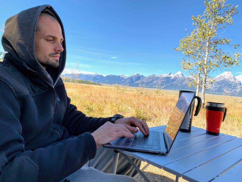 man working on laptop while camping at Grand Teton National Park