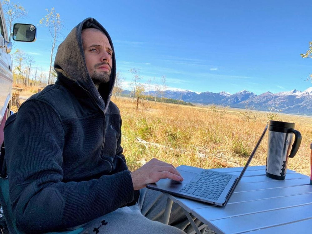 man working on his van life jobs from his laptop in Grand Teton National Park
