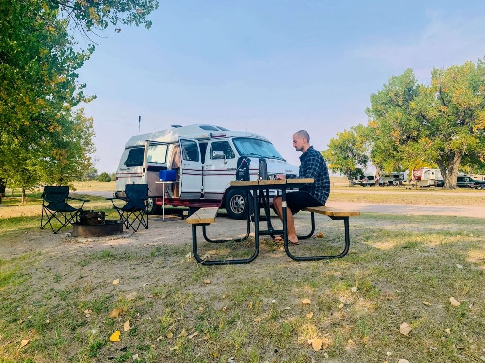 guy working at picnic table showing how to make money living in a van