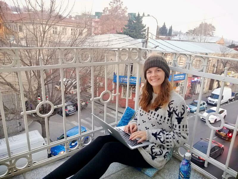 girl doing her content writing work on a laptop from a balcony in Tbilisi, Georgia