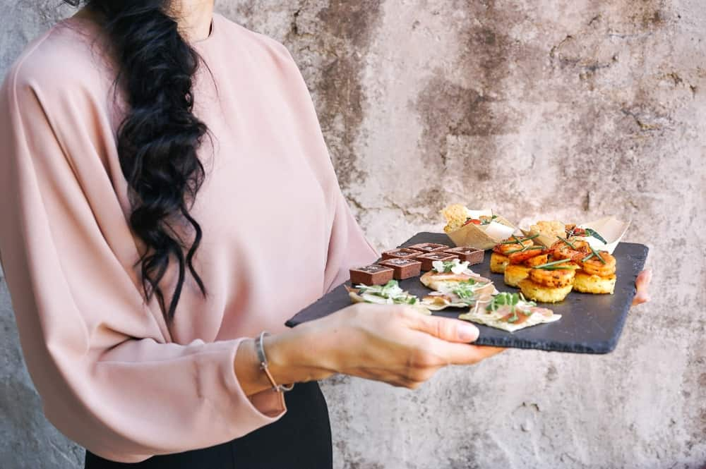traveling waitress carrying a platter of food