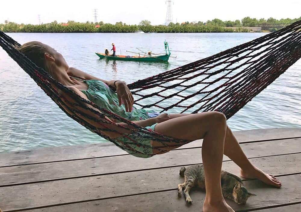 remote graphic desinger laying in hammock overlooking the river