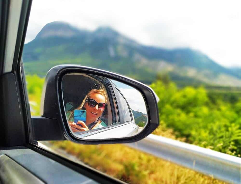 traveling graphic designer on a road trip looking in her car mirror