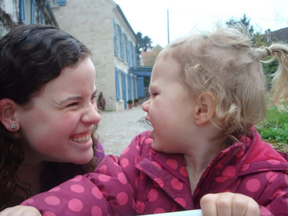 making a little girl laugh during a travel nanny job