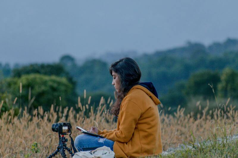 woman sitting in nature with camera
